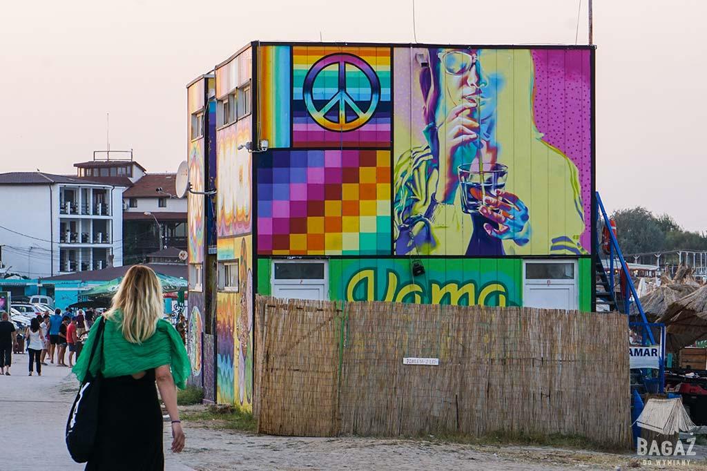 kobieta idąca w stronę kolorowych graffiti namalowanych na barach plażowych w vama veche