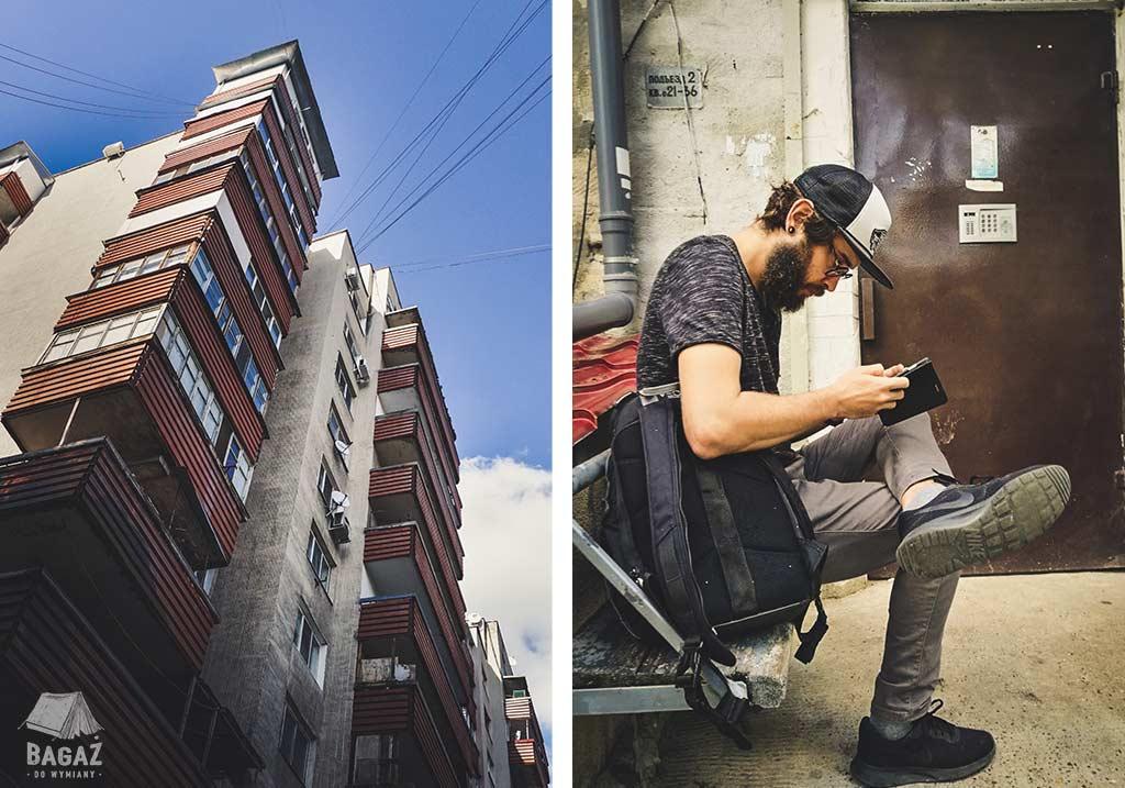 blok mieszkalny i mężczyzna z brodą siedzący na ławce