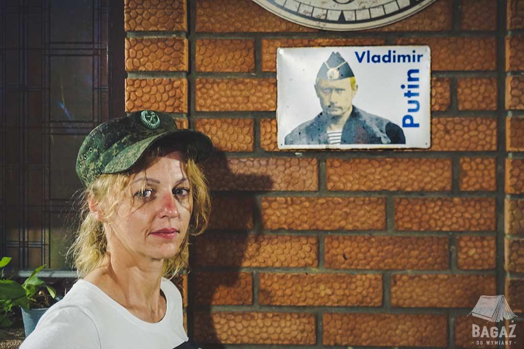 kobieta w wojskowej czapce na tle ściany z podobizna vladimira putina tyraspol