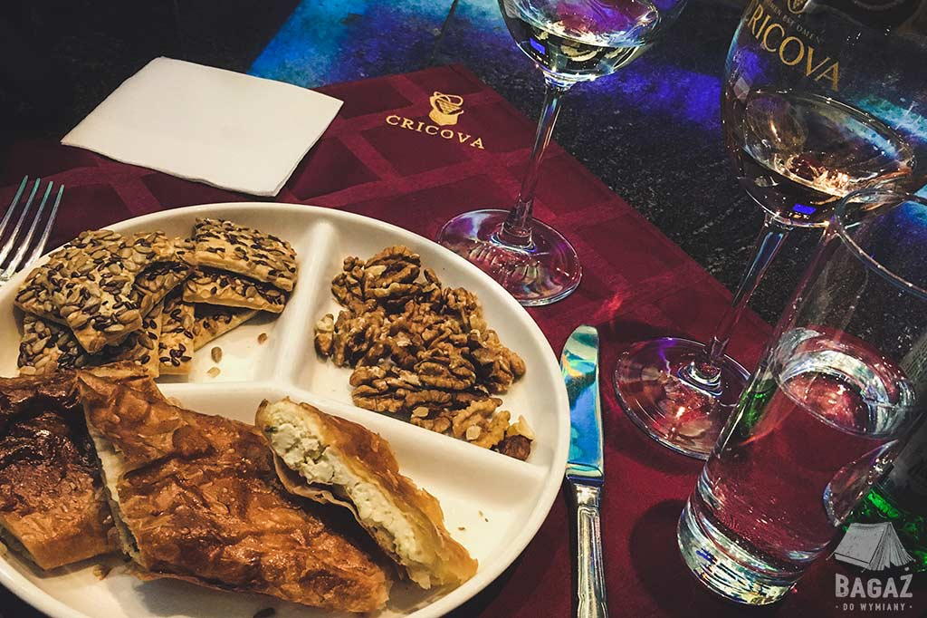talerz ze smakołykami i kieliszki z winem podczas degustacji w winnicy cricova