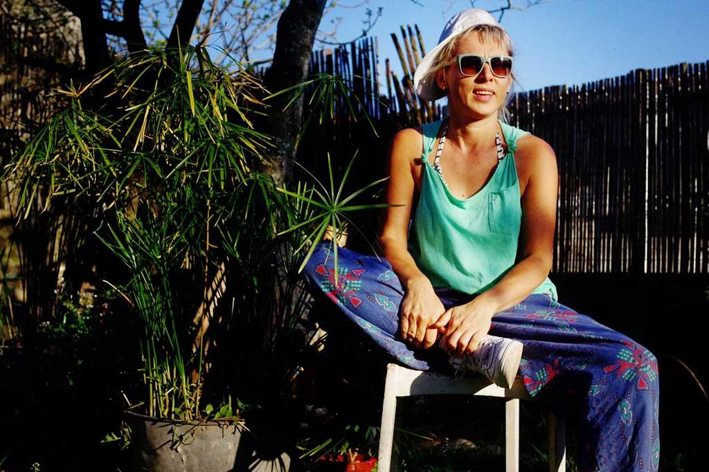 blond kobieta siedząca na krześle w ogrodzie