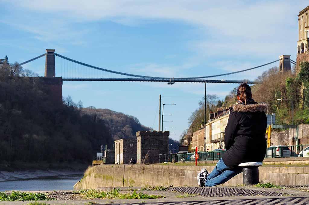 kobieta patrząca na Clifton Suspension Bridge w czasie pandemii koronawirusa