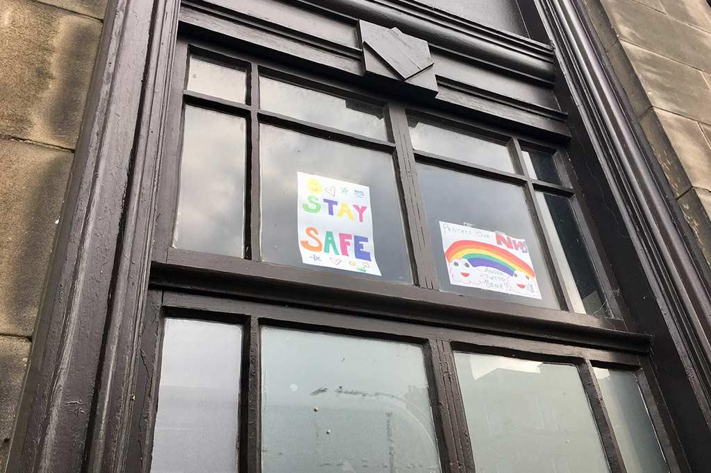 """znak """"stay safe"""" na oknach domów w edynburgu w trakcie trwania epidemii koronawirusa"""