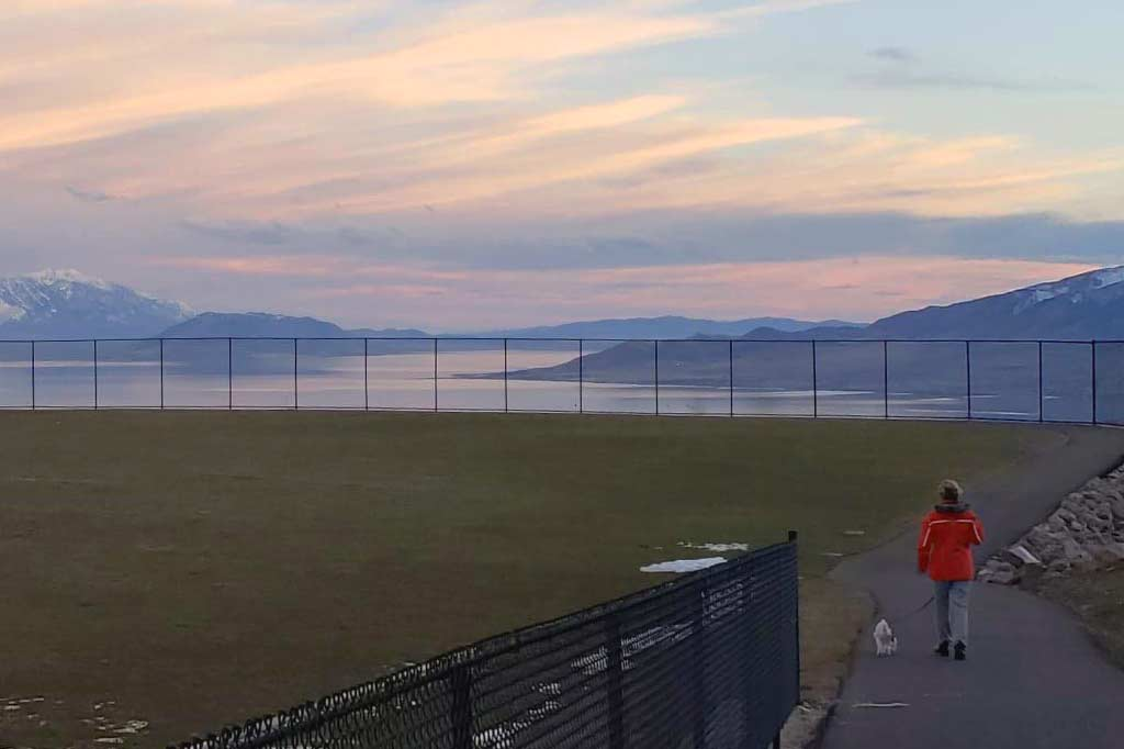 kobieta na spacerze z psem na tle zachodzącego słońca w draper w stanach zjednoczonych